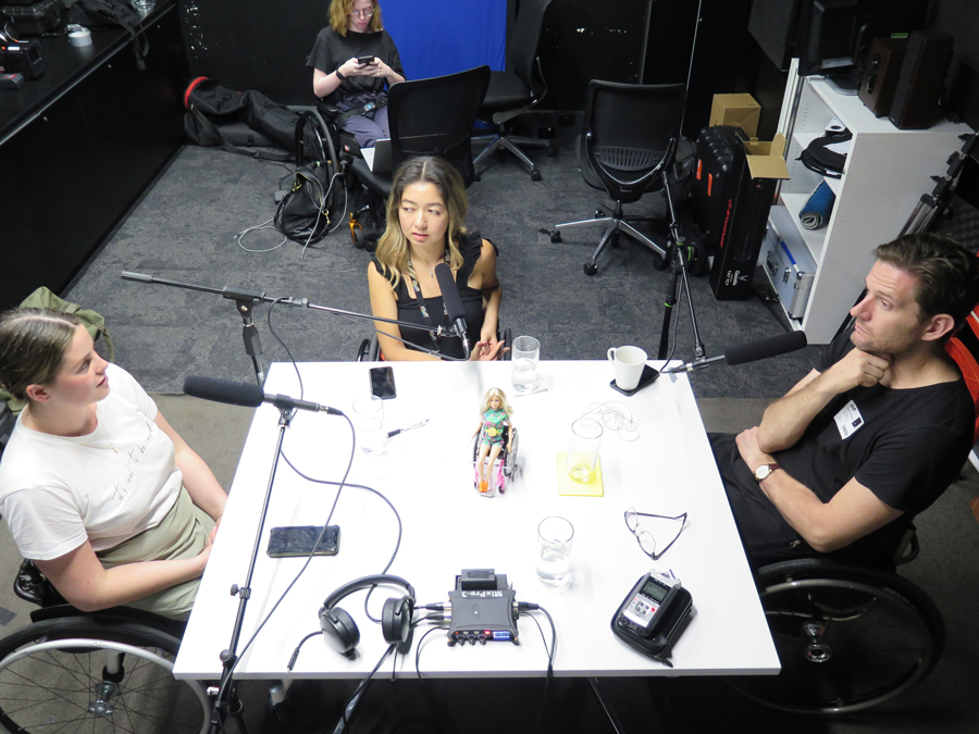 Rebecca, Olivia and Dan are three wheelchair-users sitting around a table in a studio with microphones having a discussion. Grace, also a wheelchair-user, sits in the background using her phone.