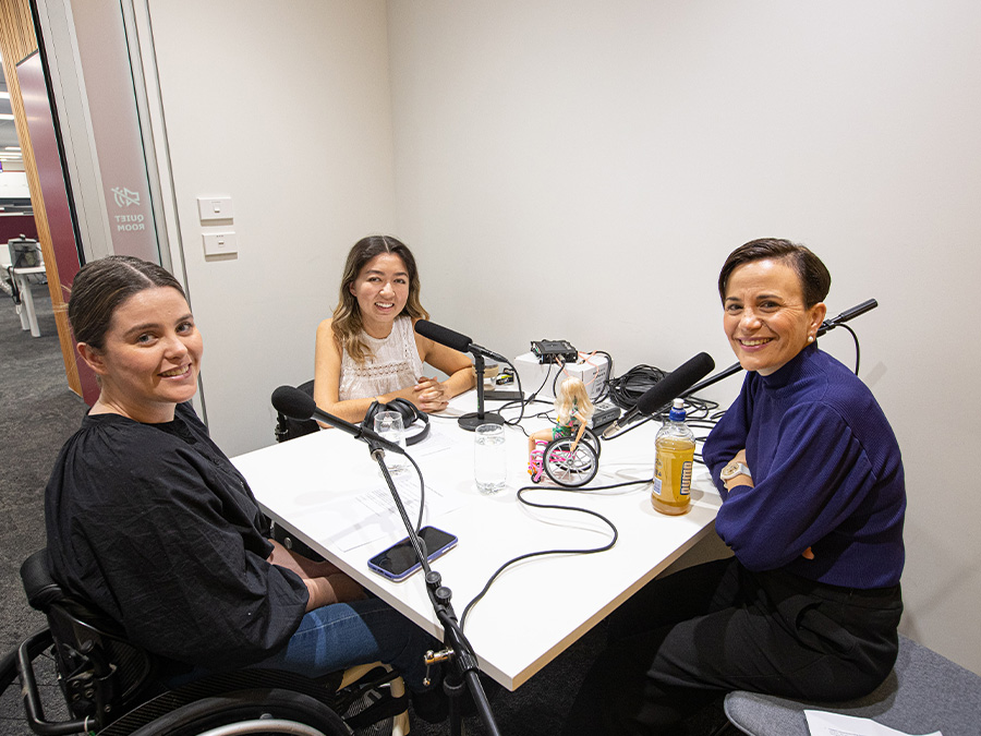 Rebecca, Olivia and Paula sit in a small meeting room around a table with microphones. Paula is seated on a grey chair and Olivia and Rebecca are wheelchair-users.