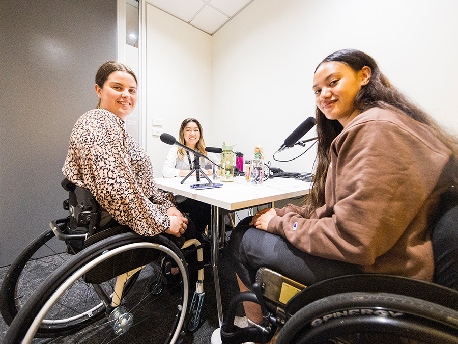Rebecca, Olivia and Chelsea sit in a small meeting room around a table with microphones. All three young women are wheelchair-users.