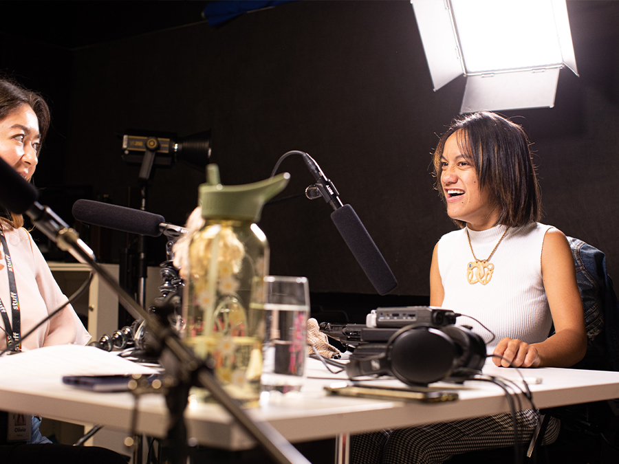 Geneva is a young Māori woman who is using a powered-wheelchair. She is smiling and is seated at a table with microphones in a studio.