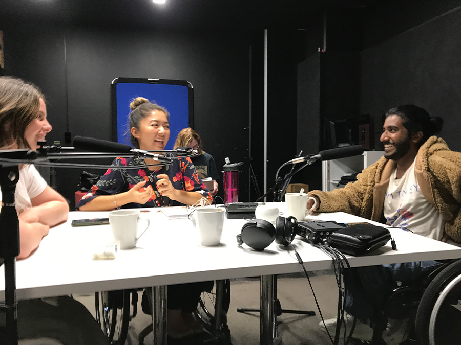 Rebecca, Olivia and Shakti are laughing while sitting around a table with microphones in a studio. They are all wheelchair-users.