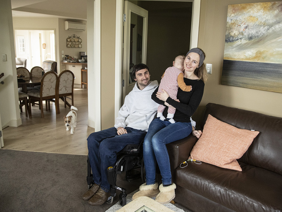 Tim is a wheelchair-user and sits next to his wife, Erica, who is holding their 5-month-old son Jasper.