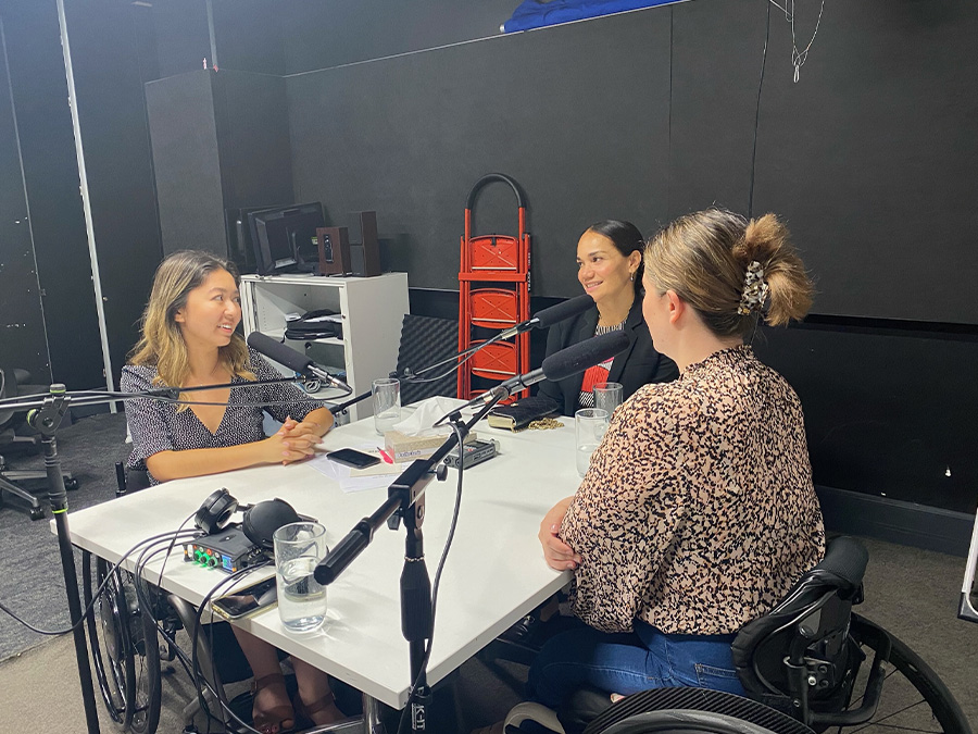 Olivia, Tiana and Rebecca in a studio sit around a table with microphones having a discussion. Olivia and Rebecca are both wheelchair-users, Tiana is Samoan.