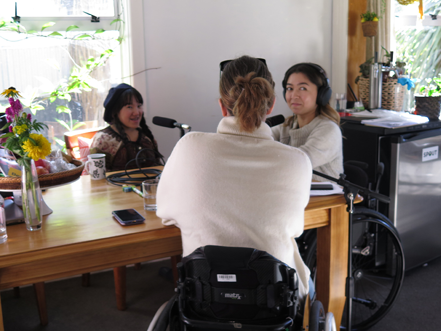 Umi, Olivia and Rebecca sit around a table in a living room. Olivia and Rebecca are sitting in wheelchairs, Umi is Japanese and sitting on a wooden chair. There are yellow and pink flowers in a vase on the table.