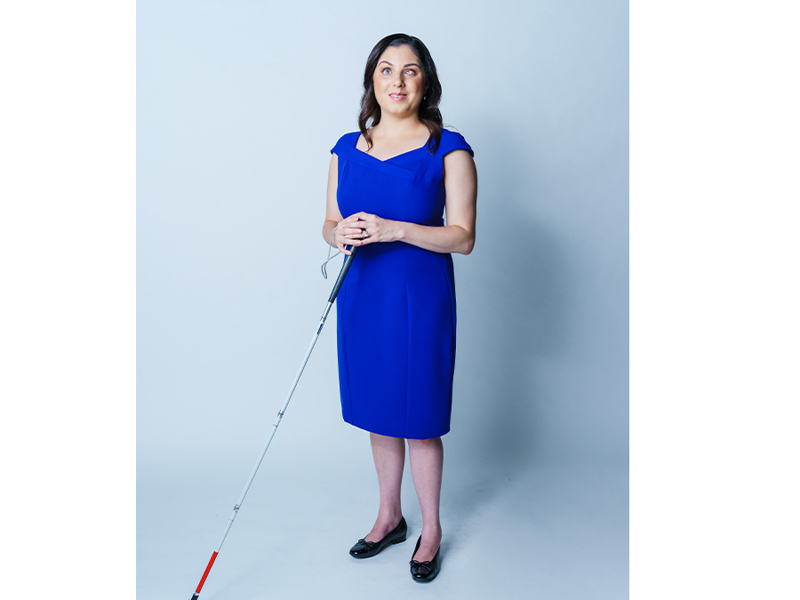 Nas is a white woman with brunette hair. She wears a bright blue dress and is holding a walking cane.