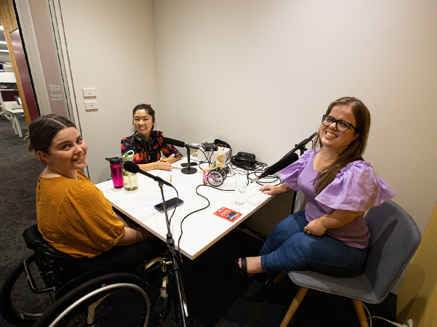 Rebecca, Olivia and Loren sit in a small meeting room around a table with microphones. Loren is short-statured, and Olivia and Rebecca are wheelchair-users.