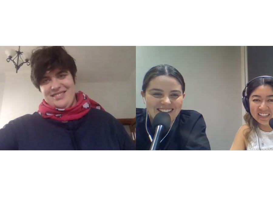 Zoom video screenshot of Henrietta, Olivia and Rebecca on a video call. Henrietta has short brunette hair and wears a red scarf. Rebecca and Olivia are smiling in front of microphones and wear headphones.