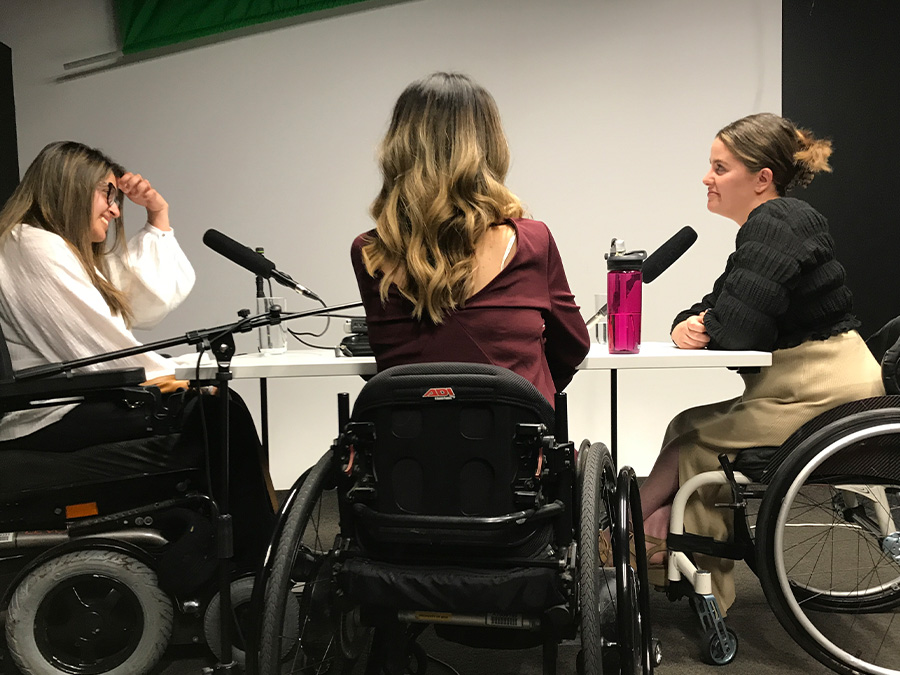 Latifa, Olivia and Rebecca sit around a table with microphones in a studio. All three young women are wheelchair-users.