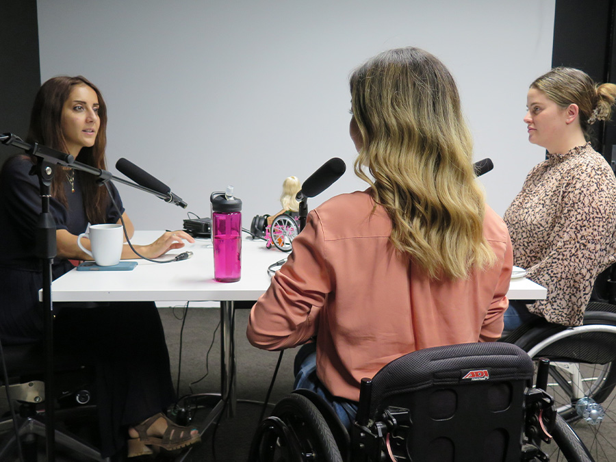 Golriz, Rebecca and Olivia sit around a table with microphones in a studio. Golriz is talking into the microphone.