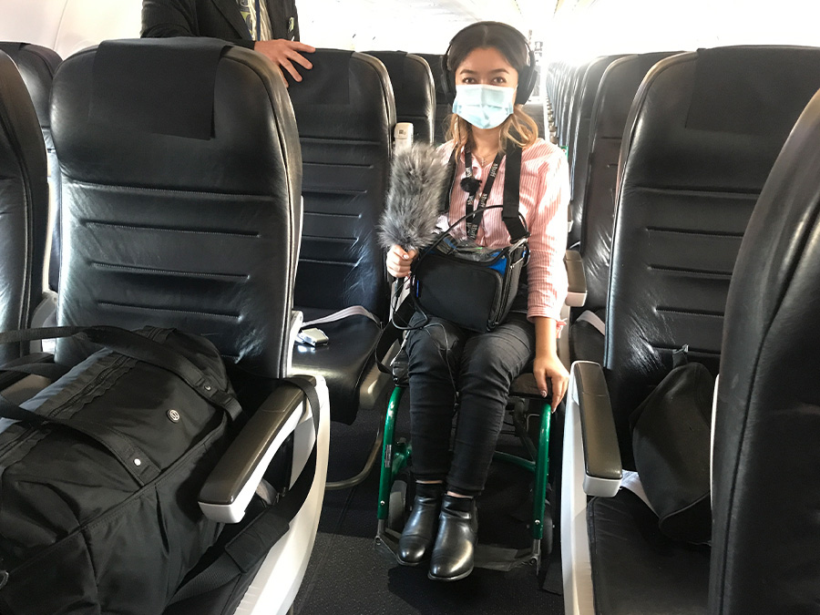 Olivia is seated in a skinny, aisle wheelchair on the airplane. She is wearing a face mask and carrying recording equipment.