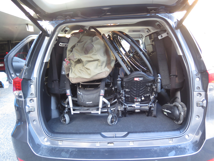 The boot of an SUV car, there are three wheelchairs collapsed in and bags around it.