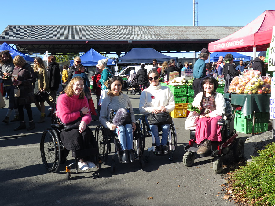 Grace, Olivia, Becs and Umi sit in a row in their wheelchairs at the Farmer's Market; they are smiling at the camera. It is a sunny day and there are stalls selling fruit and vegetables.