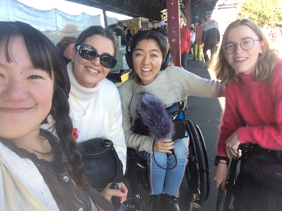 Umi takes a selfie of herself, Becs, Olivia and Grace at the Farmer's Market. Olivia is holding a recording microphone.