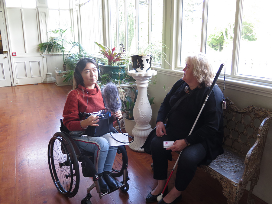 Olivia holds a microphone and recorder and interviews Julie, who is seated on a bench and holds a walking cane. They are sitting in a conservatory-looking hallway.