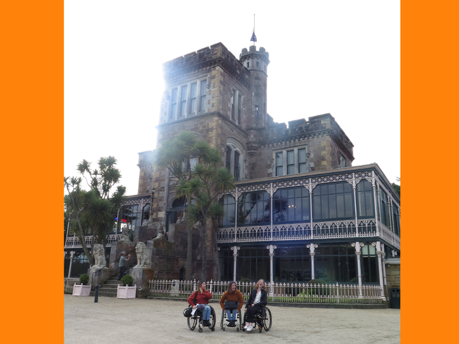 Olivia, Becs and Grace (all wheelchair users) are posed outside a large castle; they are all smiling and laughing.