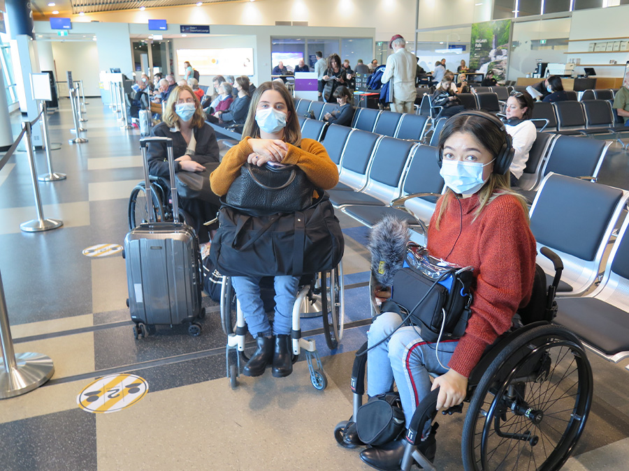 Olivia, Becs and Grace (all wheelchair users) are waiting in an airport lounge in Dunedin. They are wearing facemasks and holding their luggage.