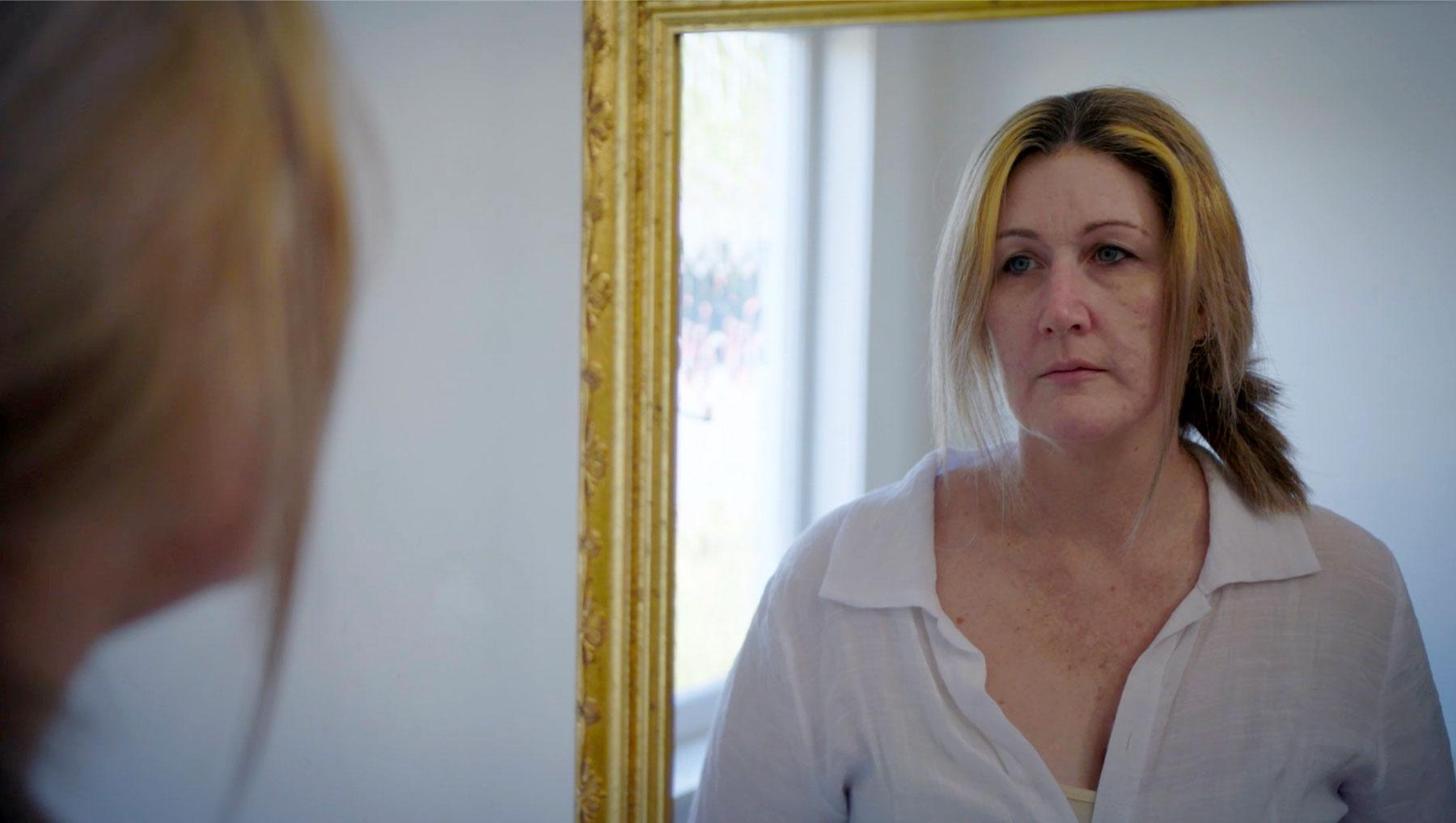 Debbs Murray looking in a mirror